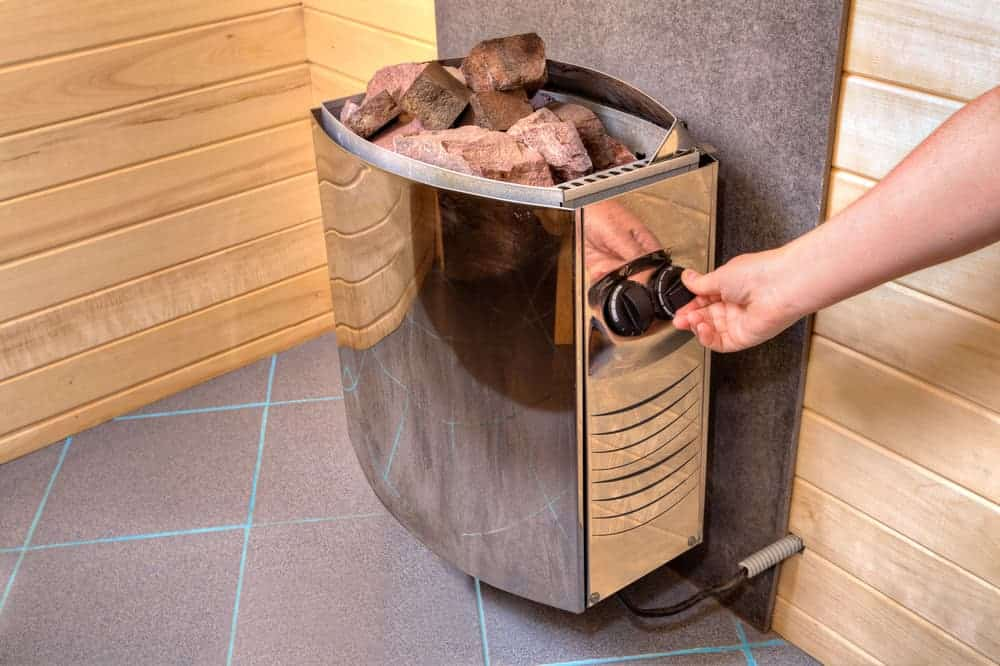 electric-sauna-heater-stove-with-stones-placed-on-top-of-it-5941478